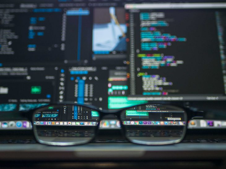 glasses in frot of code on a computer screen
