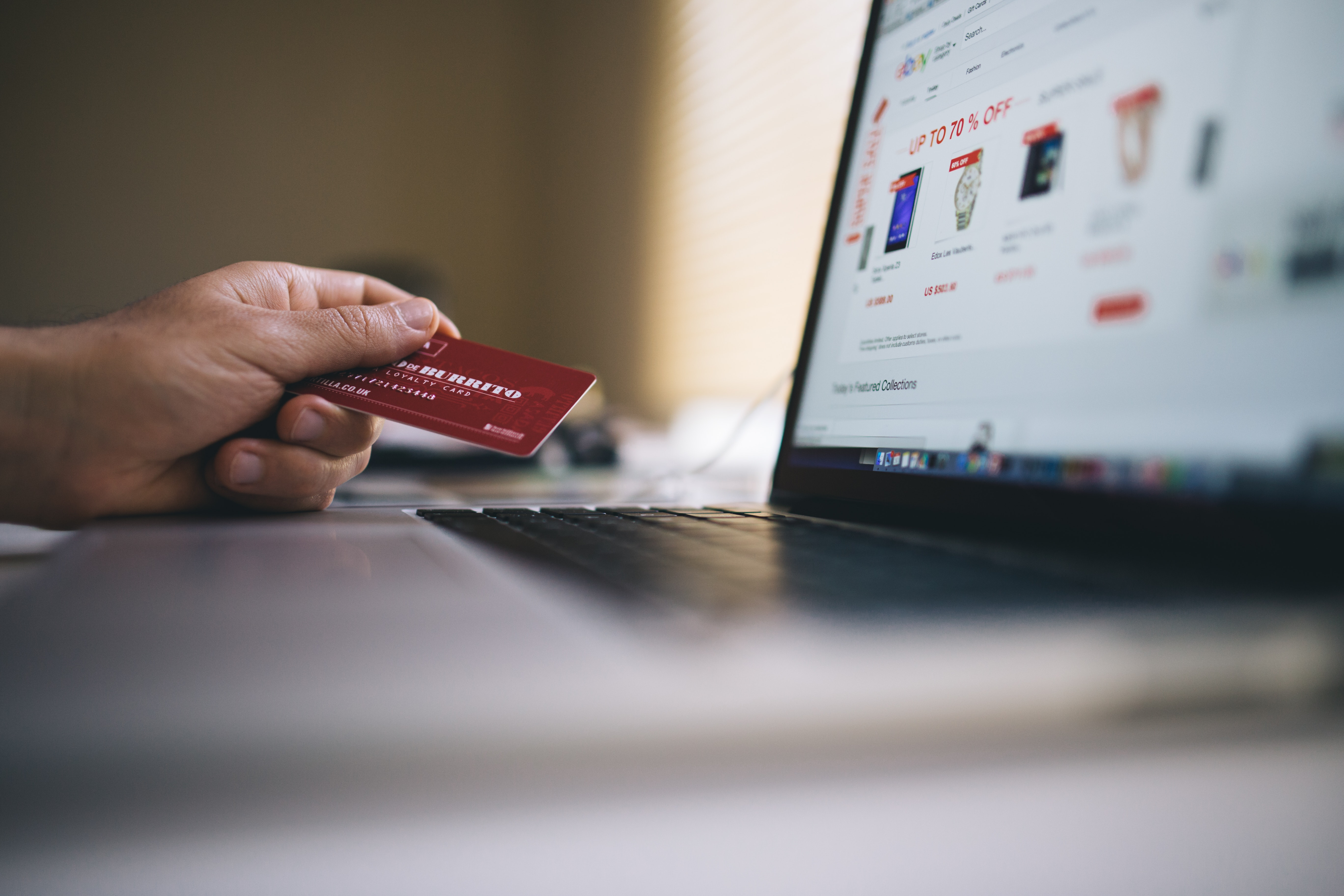 hand holding a credit card in front of a computer