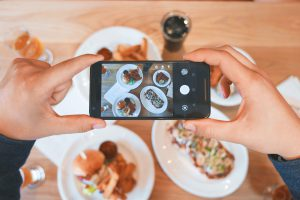 person taking a picture of food with their phone